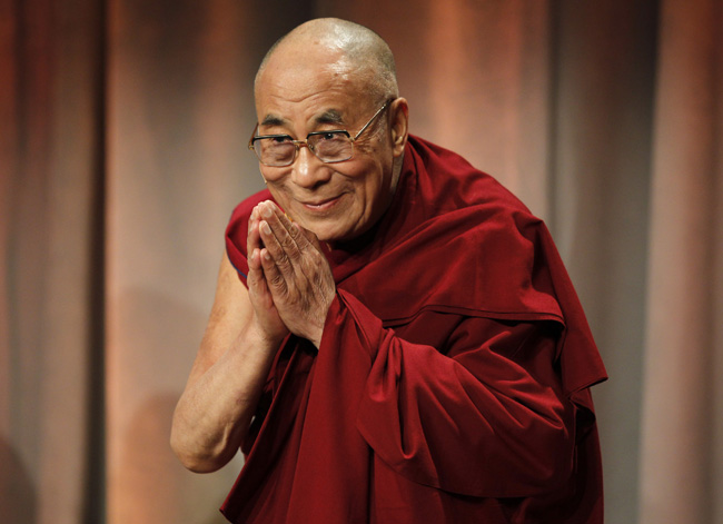 "Tibet's exiled spiritual leader the Dalai Lama greets the audience as he arrives at a talk titled ""Beyond Religion: Ethics, Values and Wellbeing"" in Boston, Massachusetts October 14, 2012. REUTERS/Jessica Rinaldi (UNITED STATES - Tags: RELIGION SOCIETY) - RTR3956W"